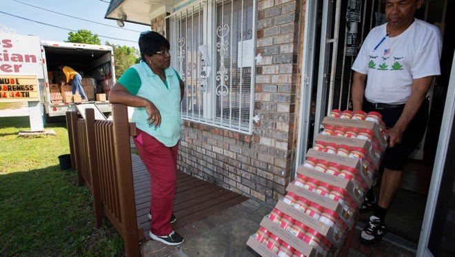 Sylvia Tisdale, the pastor at Epps Christian Center, center, looks on as Lance Guy, right, and Steven McCary, unload a shipment of food to the Pace Blvd. soup kitchen Thursday, April 12, 2018. Epps will host its 12th annual Homeless Awareness Day on Sat. April 14, 2018.