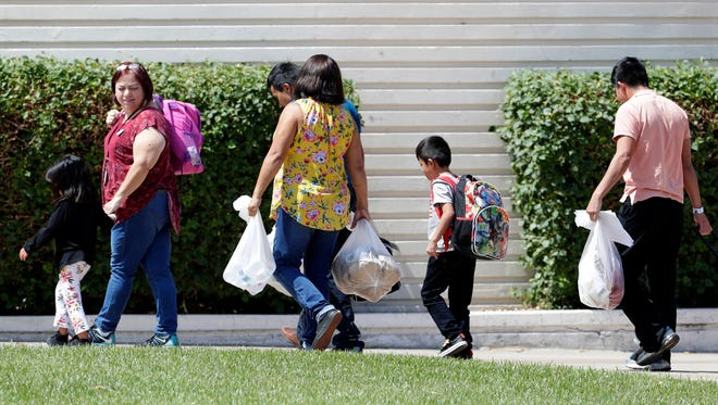 Children arrive with adults and Lutheran Social Services workers at Lutheran Social Services, Thursday, July 26, 2018, in Phoenix.