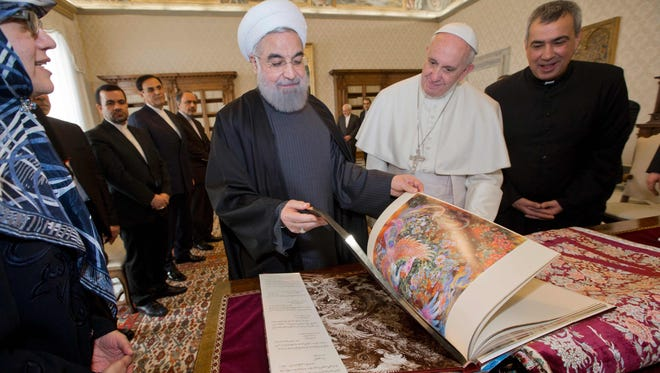 Pope Francis and Iranian President Hassan Rouhani exchange gifts during their private audience on Jan. 26, 2016, at the Vatican.