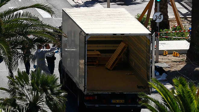 Police officers work at the  truck that mowed through revelers in Nice, southern France, Friday, July 15, 2016.