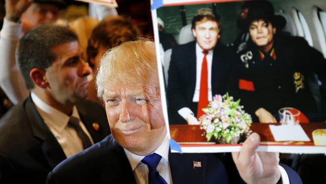 Presidential candidate Donald Trump  shows off a photo of him and Michael Jackson handed to him by a supporter during a campaign rally at the Savannah Center in West Chester Township, Ohio, on Sunday, March 13, 2016. Trump stopped in West Chester after canceling a previously scheduled rally in Cincinnati.