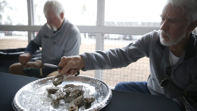 Arlo Kelly, right, and Tim Jordan shuck oysters from TCC's aquaculture studies program Monday for guests at the opening of the college's new Wakulla Environmental Institute facility off of Crawfordville Highway.