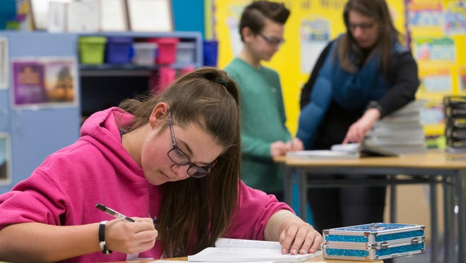 Seventh-grader Kylie Schmitting works on a religion class assignment at Chilton Area Catholic School while teacher Sabrina Holden (right) helps seventh-grader Jack Feider with a question on Feb. 16, 2017, in Chilton, Wis.