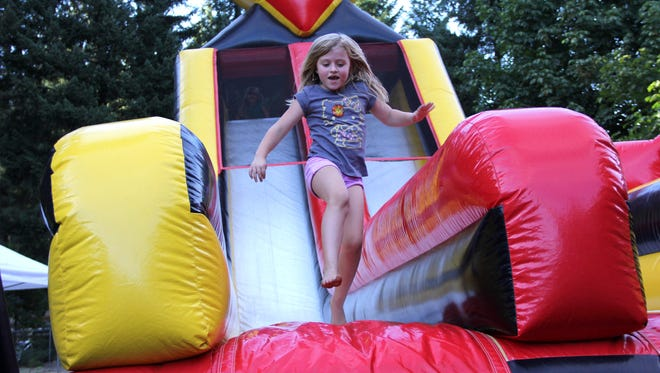 Amelia Sky slides down an inflatable slide at the Detroit Lake Eclipse Fest.