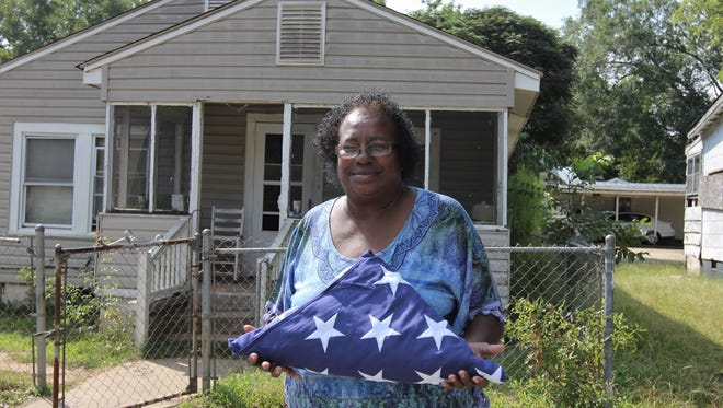 Margaret Lewis holds a flag from her deceased sister, retired Air Force Col. Mary Boyd, in front of the Anderson home where they were raised.