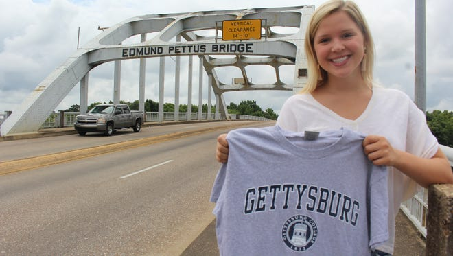 Selma native Ali Nettles, a sophomore at Gettysburg College, holds a Gettysburg T-shirt on the Edmund Pettus Bridge.