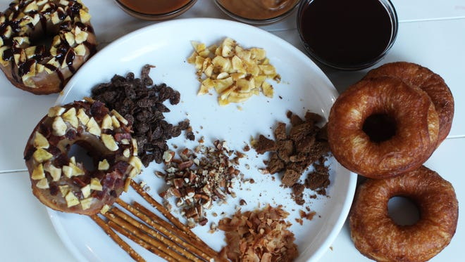 An array of toppings for doughnuts including pretzels, dried fruits, toasted nuts, toasted coconut, crushed cereal and crushed cookies, peanut butter, chocolate glaze and caramel sauce.