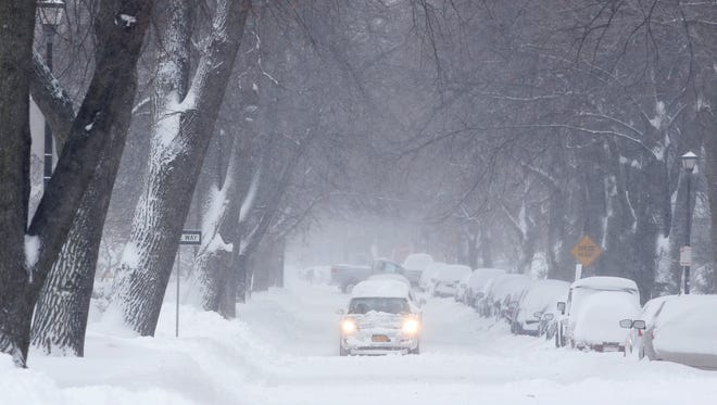 Cars drive through Rutgers Street towards Monroe Avenue during a snow storm in the Rochester area.