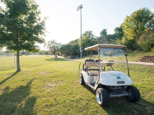 A golf cart is parked near one of the fields at Shoreline