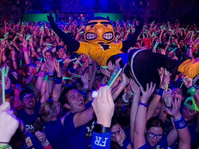 Marathoners lift Herky into a wave at the 24th annual