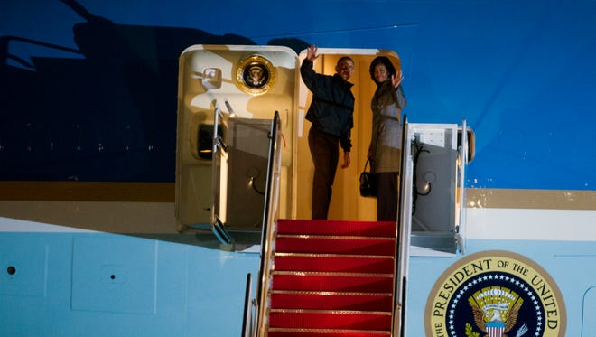 President Obama and first lady Michelle Obama wave from Air Force One before departure, at Andrews Air Force Base, Md., on Jan. 24, 2015, for a trip to New Delh by way of Ramstein Air Base, Germany.