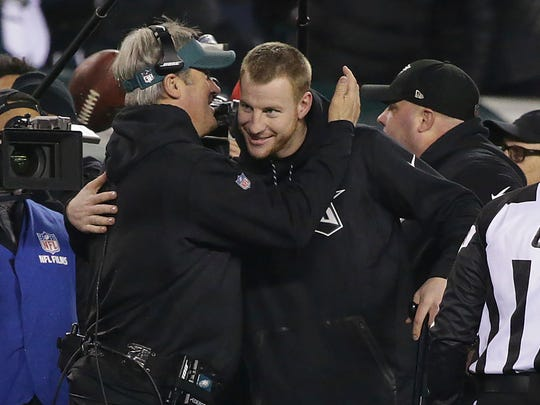 Eagles coach Doug Pederson, left, and injured quarterback Carson Wentz hug near the end of the Eagles' 38-7 win over the  Vikings  in the NFC championship game Jan. 21, 2018.