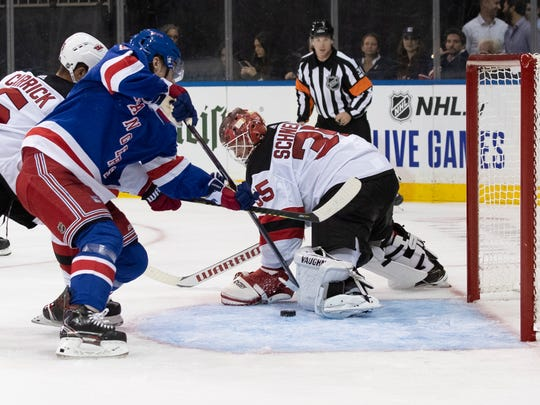 New Jersey Devils goaltender Cory Schneider (35) makes a save against New York Rangers center Lias Andersson during the second period of a preseason NHL hockey game Wednesday, Sept. 18, 2019, at Madison Square Garden in New York. (AP Photo/Mary Altaffer)