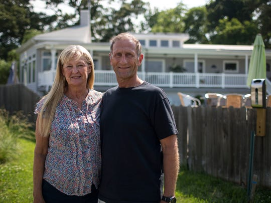 Debbie Miller and husband Gary Chiaverotti, seen May 28, 2014 in front of their Norfolk, Virginia home along the Lafayette River, received funding from the Federal Emergency Management Agency to add four feet to their home's foundation because of the risk of floods.