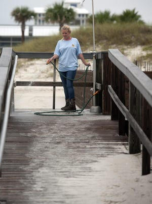 """Santa Rosa Island Authority maintenance worker, Amanda Burnette, cleans away the wind blown sand from the Casino Beach area in preparation of Tuesday night """"Bands on the Beach"""" concert. The SRIA maintenance crews start working before daybreak most days."""