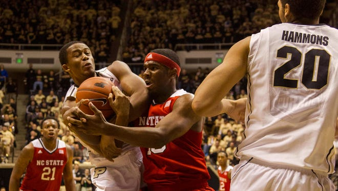 Dec 2, 2014; West Lafayette, IN, USA; North Carolina State Wolfpack guard Chris Corchiani Jr. (13) and Purdue Boilermakers forward Basil Smotherman (5) fight for a rebound in the first half at Mackey Arena. Mandatory Credit: Trevor Ruszkowski-USA TODAY Sports