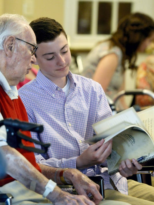 "Country Meadows resident Ed Flick, 91, and Dallastown eighth-grader Robby Brown look through a ""keepsake book"" that Robby filled in based on interviews with Flick on Friday at Country Meadows of York-South in York Township."