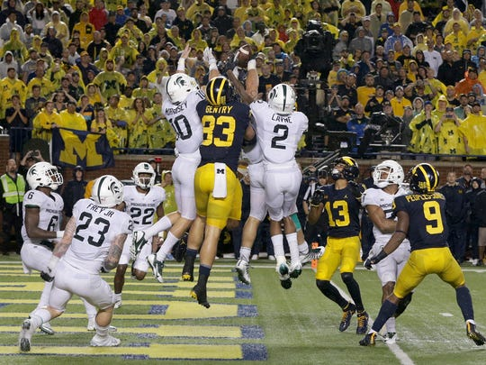 Michigan and Michigan State players jump for the football on Michigan quarterback John O'Korn's Hail Mary throw into the end zone on the game's final play. The ball fell to the ground, giving Michigan State a 14-10 win at Michigan Stadium in Ann Arbor on Oct. 7, 2017.