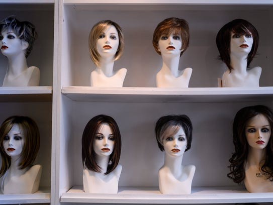 A wall of wigs are displayed for customers at The Cottage