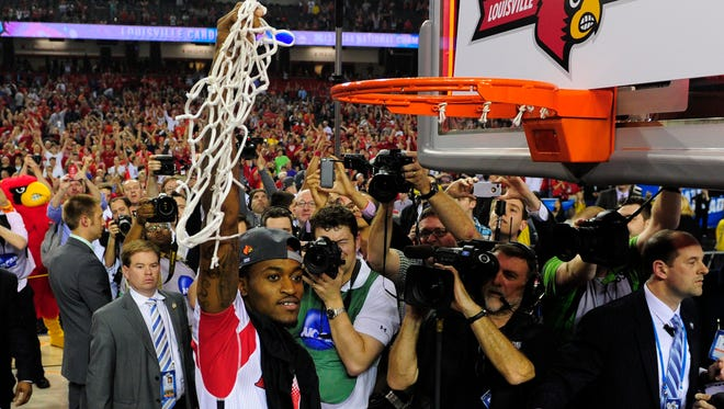 Louisville guard guard Kevin Ware celebrates after the Cardinals beat Michigan to win the 2013 men's basketball championship.