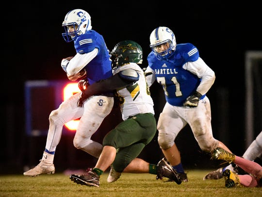 Sartell quarterback Christopher Belling, left, is stopped