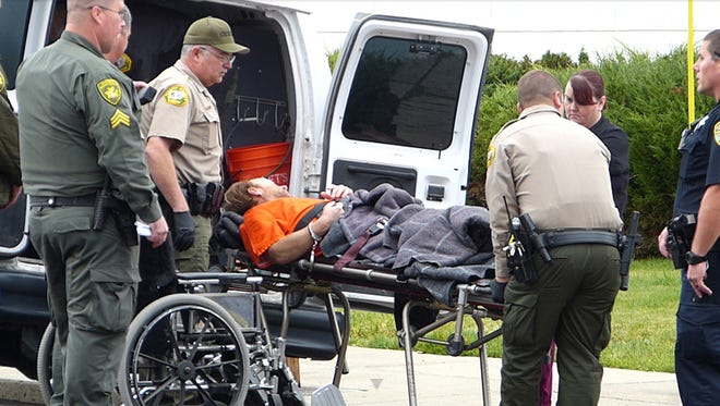 Law enforcement officers unload Jack Lee Breiner, accused of killing a Modoc County deputy Jack Hopkins, for his arraignment Friday in Modoc County Superior Court in Alturas, Calif. Breiner pleaded not guilty to the charges.