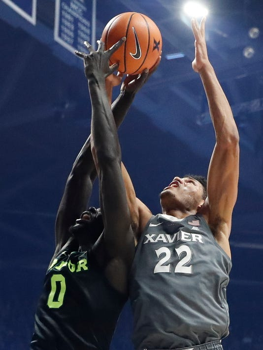 RETRANSMISSION TO CORRECT TEAM - Xavier's Kaiser Gates (22) and Baylor's Jo Lual-Acuil Jr. (0) battle for a rebound in the first half of an NCAA college basketball game, Tuesday, Nov. 28, 2017, in Cincinnati. (AP Photo/John Minchillo)