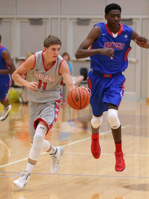 Indiana's Ryan Cline brings the ball up court under the pressure of Kentucky's Ray Spaulding during the Junior All-Star Game, Friday, June 6, 2014, at Greenfield Central High School.