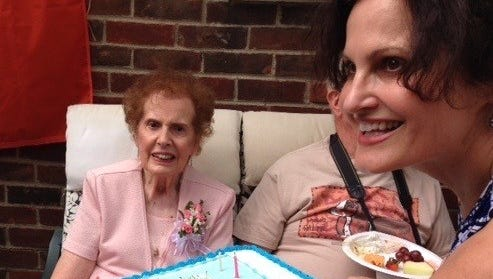 Cathy Washabaugh presents the birthday cake to her 90-year-old mother, Sheila Becker, at her birthday party. Guests helped her celebrate decades of her life with happy memories.