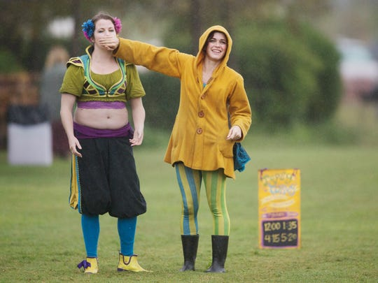 Comedic performers Amanda Renaud, left, and Lily Hufnagel keep their act fresh while waiting out a rain delay Saturday at the Riverdale Kiwanis Medieval Faire at Lakes Regional Park in south Fort Myers. activities. The faire continues Sunday and next weekend.
