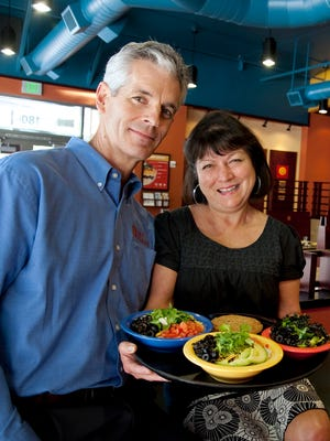 Cafe Yumm! co-founders Mark and Mary Ann Beauchamp pose with a selection of Yumm! bowls. Most Yumm! bowls come with a selection of vegetarian toppings, including avocado, beans, cilantro, tomatoes and salsa.