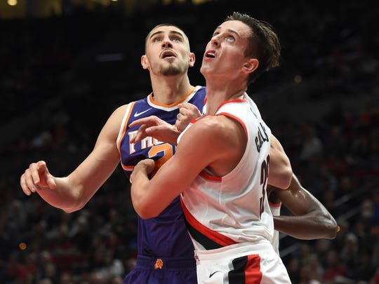 Phoenix Suns center Alex Len, left, and Portland Trail Blazers center Zach Collins wait for a rebound during the second half of an NBA basketball preseason game in Portland, Ore., Tuesday, Oct. 3, 2017. The Suns won 114-112.