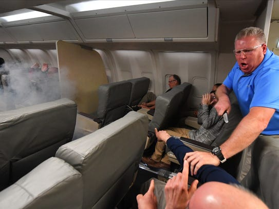 Trainers in the role of terrorists, one holding a knife and another in a window seat attempting to light an explosive, try to take over a mock plane as an air marshal approaches from the left during training May 9, 2018, in Egg Harbor Township, N.J.