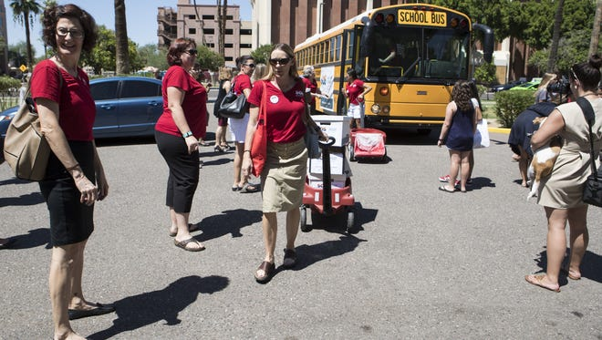 Karen Gresham helps deliver signatures to the Arizona Secretary of State's Office on Aug. 8, 2017, in Phoenix. Save Our Schools Arizona gathered more than 111,000 signatures to temporarily block the expansion of the state's school-voucher program.