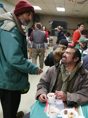 Willie Staephens, left, greets Donald Santillanez during a Christmas Eve lunch on Thursday, Dec. 24, 2015, at the Union Gospel Mission in Salem, Ore. The event featured live music and handmade decorations.