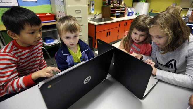 In November, second-grader Josh Mercado, left, helps kindergartner Erik Hodges, and other students during their weekly computer science lesson at Marshall Elementary School in Marysville, Wash.