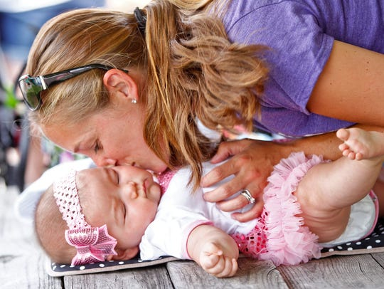 Colleen Patch, of Conklin, kisses her 7-month-old daughter,