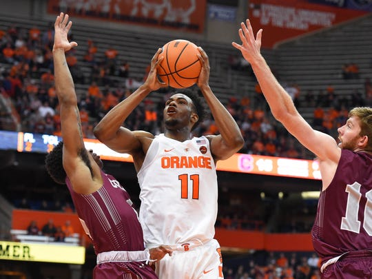Syracuse Orange forward Oshae Brissett (11) shoots the ball between Colgate Raiders guard Jordan Burns (1) and forward Will Rayman (10) during the second half at the Carrier Dome.