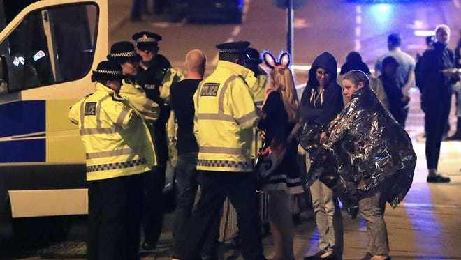 Emergency services personnel speak to people outside Manchester Arena after an explosion at the venue during a May 22 Ariana Grande concert in Manchester, England,