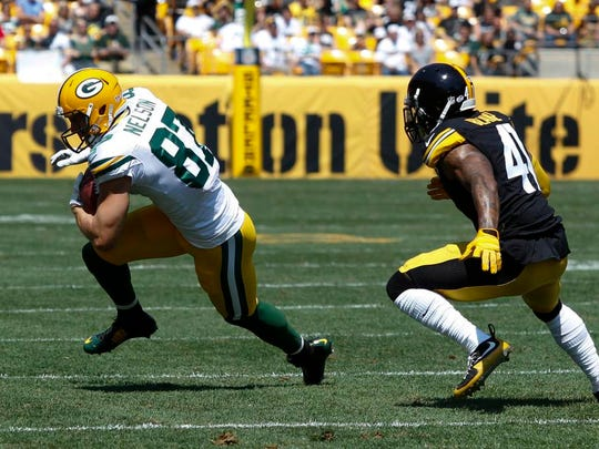 Green Bay Packers wide receiver Jordy Nelson (87) runs after a pass reception against Pittsburgh Steelers defensive back Antwon Blake (41) during the first quarter at Heinz Field.  Nelson was injured on the play.