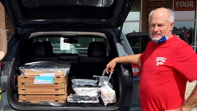 Phil Repp, of Gionino's in Twinsburg, with some of the food donated to police and firefighters recently by a neighbornood in Twinsburg that asked to remain anonymous. The residents took up a collection and were able to feed three fire department shifts and two police department shifts. Over three days, Gionino's delivered seven sheet pizzas, 350 wings and five trays of salad. One neighbor baked 160 cupcakes for dessert. The neighborhood hoped to be an inspiration to others in supporting the safety forces.