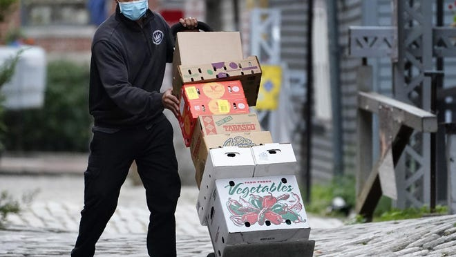 Jenzy Guzman wears a mask to help prevent the spread of the coronavirus while making deliveries to restaurants in the Old Port, Tuesday, Oct. 13, 2020, in Portland, Maine.
