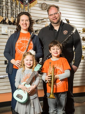 Bellevue's Bandwagon Music and Repair, was awarded $20,000 as part of the Synchrony Financial Working Forward Small Business Awards. Store owners Linden and Jennifer Lantz are pictured with their children after receiving the award on Jan. 3, during a presentation at their store located at 7639 Hwy 70 S in Bellevue.