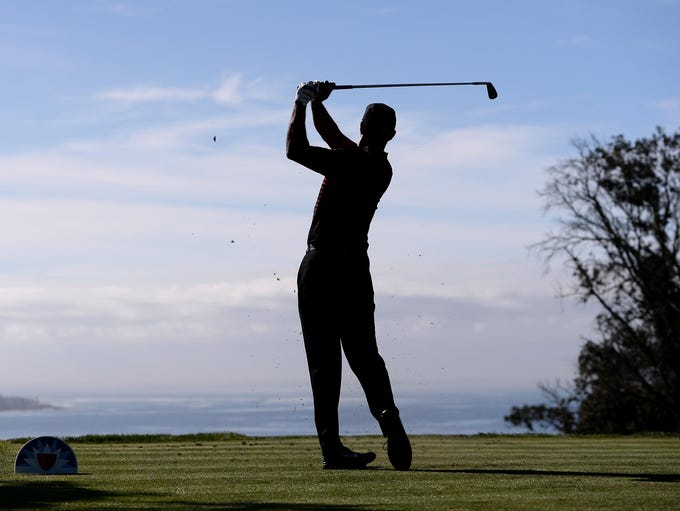 Tiger Woods plays his shot from the third tee during