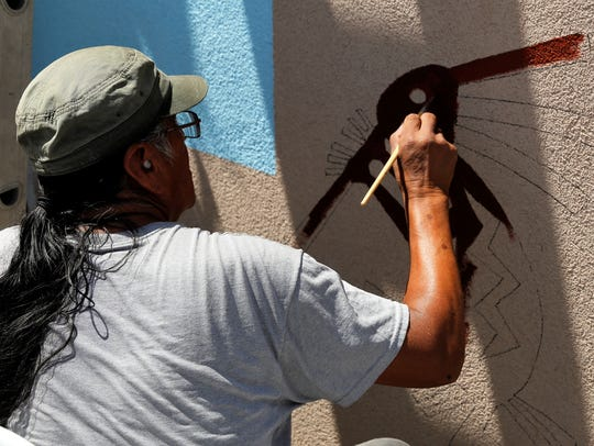 Eugene B. Joe paints a Kokopelli figure that is part