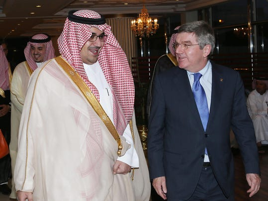 """This image released by the Saudi Press Agency shows Prince Nawaf Faisal Fahd bin Abdul-Aziz, an International Olympic Committee member and president of the national Olympic committee, left, walking with IOC President Thomas Bach, right, in Riyadh, Saudi Arabia, Wednesday, April 2, 2014. IOC President Thomas Bach has discussed the issue of women's participation in sports with Saudi Arabia's Olympic chief. The IOC says Wednesday that Bach promised """"full support"""" for the country's sports development strategy through 2020. The plan includes """"proposals to increase women's participation in the Olympic Games and in sport in general."""" Saudi women are largely banned from participating in sports in the kingdom, although there are several football and basketball clubs that play in clandestine leagues. After prolonged negotiations with the IOC, Saudi Arabia sent women to the Olympics for the first time in 2012, with two female athletes competing at the London Games. (AP Photo/Saudi Press Agency)"""