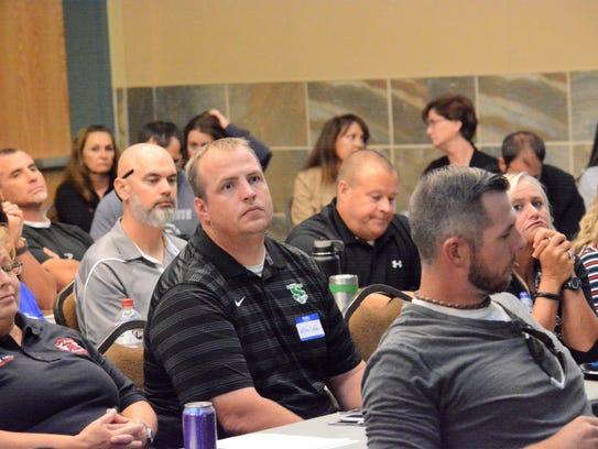Farmington football coach Jeff Dalton, center, listens
