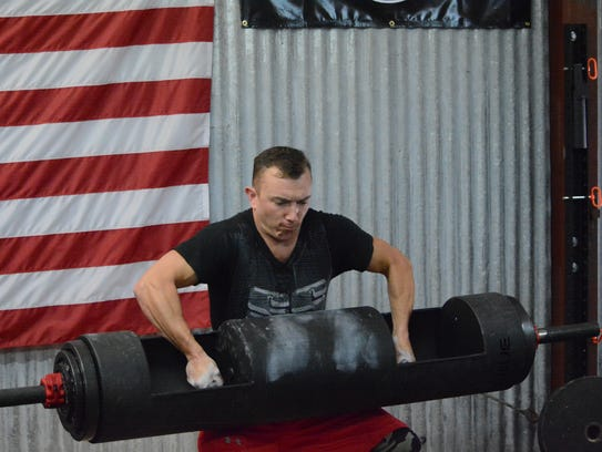 Farmington's Nick Miller prepares to thrust a heavy log above his shoulders in his second heat for the log press event during Saturday's Strongman/Strongwoman competition at American Strength and Fitness.