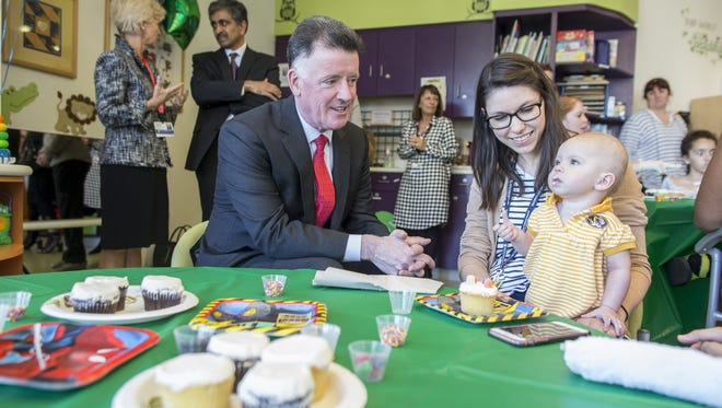 Jim Judge, Chairman, President and CEO of Eversource, left, decorates cupcakes with Catherine and mom at Boston Children's Hospital on June 7, 2017 in Boston, Massachusetts.