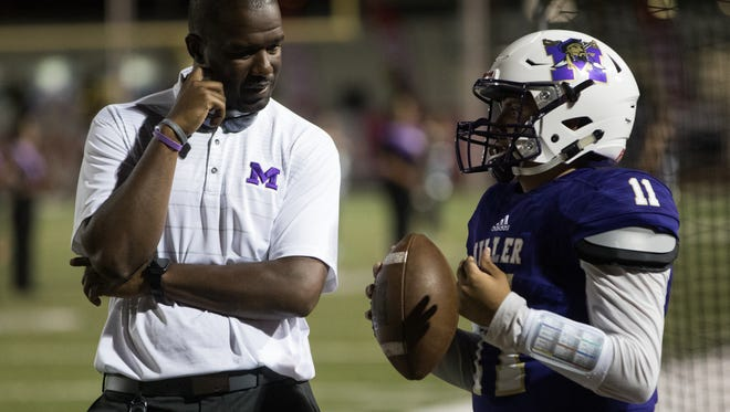 Miller's head coach Justen Evens talks with quarterback Joshua Vasquez before the start of the third quarter of their game against King at Buccaneer Stadium on Sept. 7, 2017.